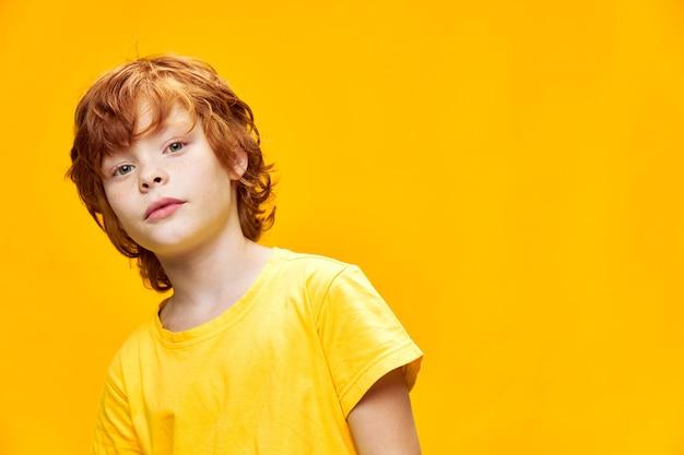 Portret rudowłosego chłopca pochylony na bok na odosobnionym tle i trzyma ręce w dół