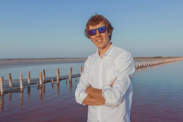 Portret rudowłosego mężczyzny w białej koszuli i okularach przeciwsłonecznych na słonym jeziorze sasyk sivash