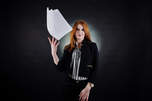 Portret rudowłosej bizneswoman w pasiastej bluzce i kurtce wyrzucający papier.