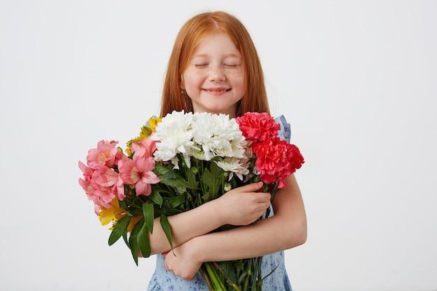 Portret rudowłosej dziewczyny o drobnych piegach, z zamkniętym bukietem i cieszącej się zapachem kwiatów, wygląda uroczo, nosi niebieską sukienkę, stoi na różowym tle.