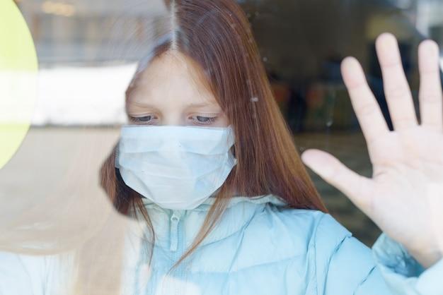 Portret rudowłosej dziewczyny przez okno w masce ochronnej jako koncepcja kwarantanny i izolacji z powodu koronawirusa covid-19, zamknięcia granicy i braku jedności społecznej w pandemii