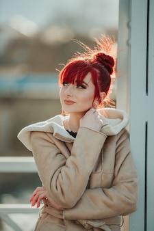 Portret rudowłosej dziewczyny z grzywką opartej o metalowy filar w wietrzny zimowy dzień