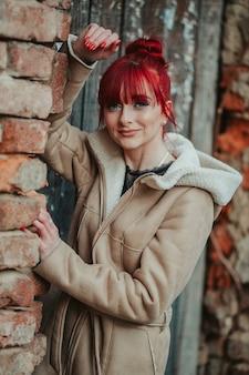 Portret rudowłosej dziewczyny z grzywką w zimowym płaszczu, opartej na ceglanej ścianie rękoma
