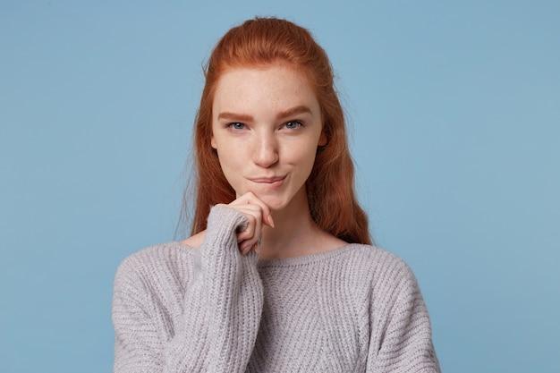 Portret rudowłosej pięknej dziewczyny z przebiegłym spojrzeniem