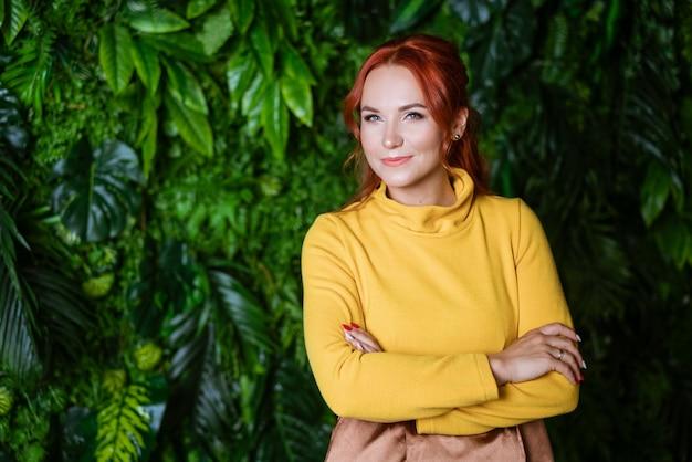 Portret rudowłosej pięknej kobiety w żółtym swetrze na zielono