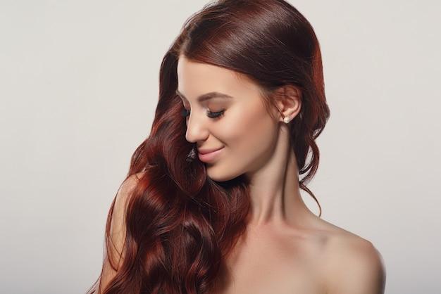 Portret rudowłosej pięknej młodej kobiety na jasnym tle