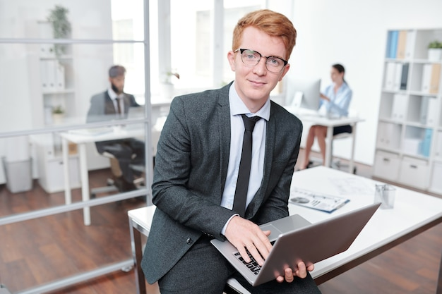 Portret rudowłosy młody biznesmen w okularach, opierając się na biurku w biurze, kopia przestrzeń