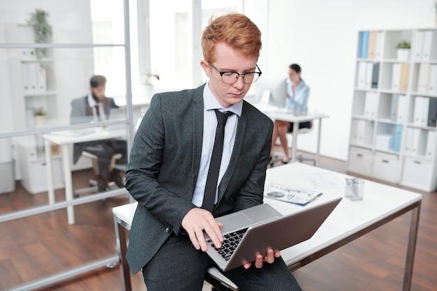 Portret rudowłosy młody biznesmen za pomocą laptopa przechyla się na biurku w biurze, kopia przestrzeń