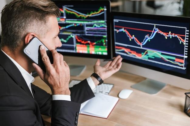 Portret rzeczowy mężczyzna 30s ubrany w garnitur mówiący przez telefon komórkowy podczas pracy z grafiką cyfrową na komputerze w biurze
