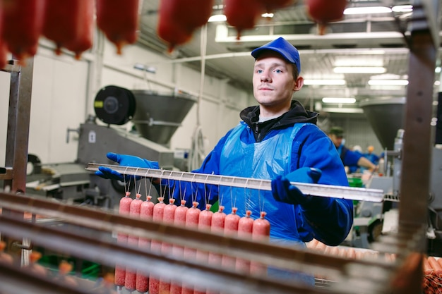 Portret rzeźnicy przetwarza kiełbasy przy mięsną fabryką