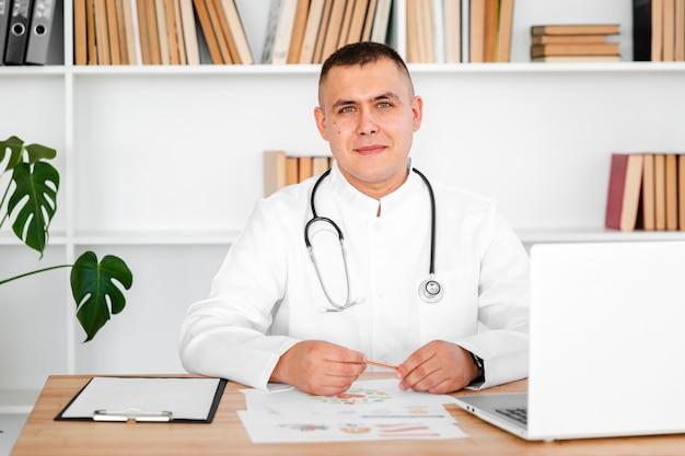 Portret samiec lekarki obsiadanie na biurku