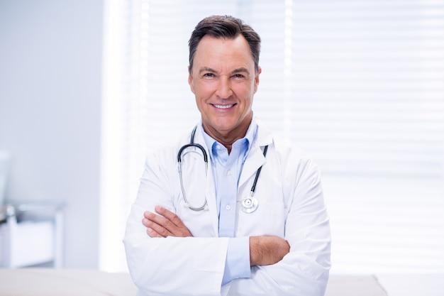 Portret samiec lekarki pozycja z rękami krzyżować