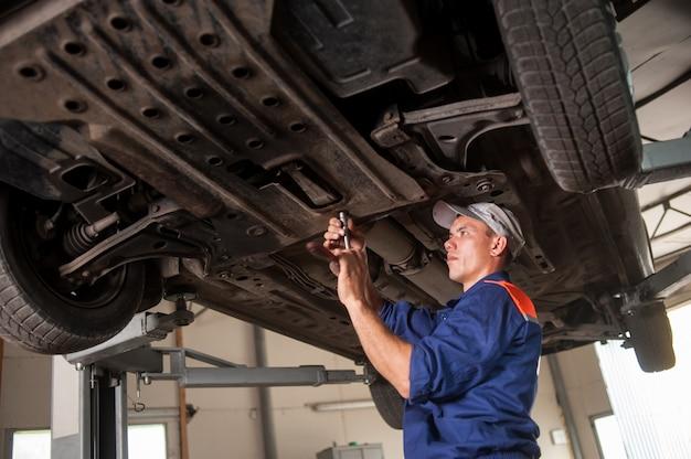 Portret samochodowy mechanik pracuje z narzędziami pod samochodem