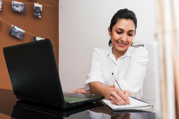 Portret samozatrudnionej kobiety notatek podczas rozmowy przez telefon z domu w jej prowizorycznym biurze