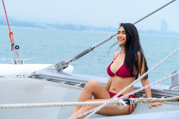 Portret seksowna azjatykcia dziewczyna w bikini kłaść puszek relaksuje na rejsu jachcie