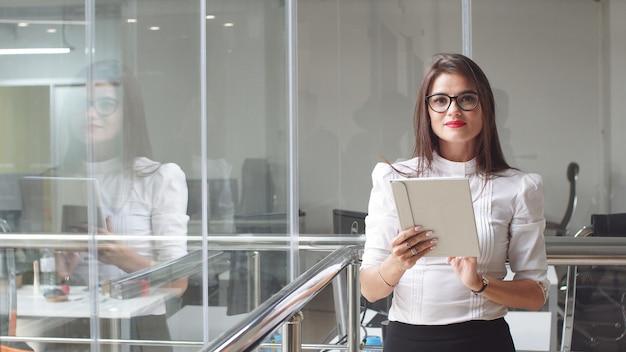 Portret seksowna biznesowa kobieta w szkłach z pastylką