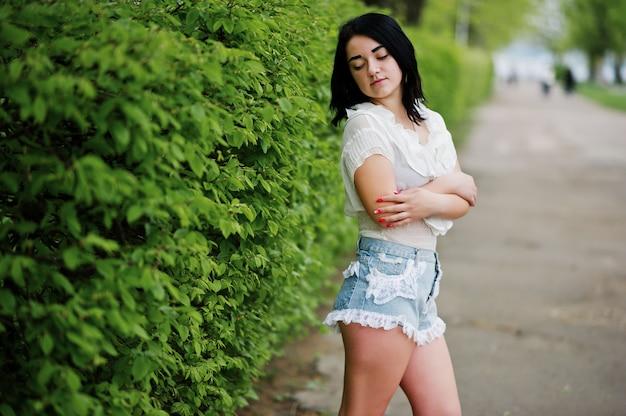 Portret seksowna brunetka dziewczyna na szorty damskie jeansy i białą bluzkę na tle zielonych krzewów wiosennych.