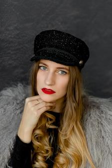 Portret seksowna dziewczyna w czarnej czapce i szarym futrze z lamy.