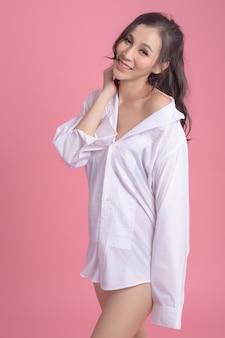 Portret seksowna kobieta ubrana w białą koszulę na różowo