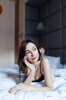 Portret seksowna młoda dama w łóżku wczesnym porankiem