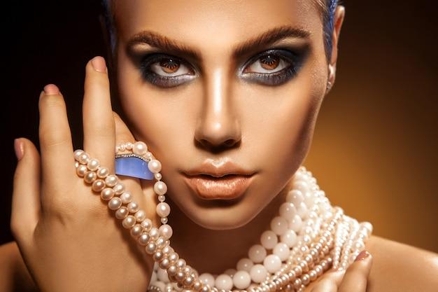 Portret seksowna, młoda, dorosła kobieta z zielonymi kolorami makijażu i perłami, patrząc na kamery
