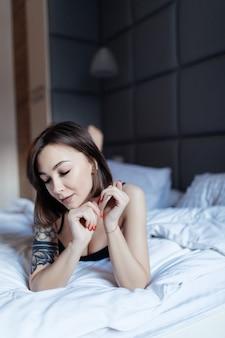 Portret seksowna młoda kobieta w łóżku wczesnym porankiem