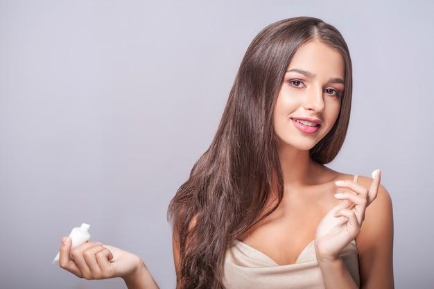 Portret seksowna młoda kobieta z kroplami kosmetyczna śmietanka na skórze pod oczami.