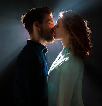 Portret seksowna młoda para w pre pocałunku ze strumieniami światła