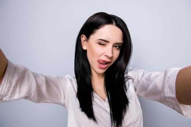 Portret seksowna piękna młoda kobieta oblizuje usta i robi selfie zdjęcie