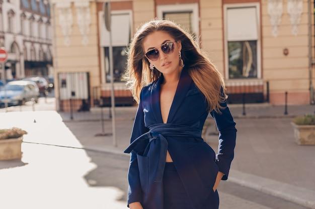 Portret seksowna stylowa kobieta spaceru na ulicy w niebieskim garniturze na sobie okulary przeciwsłoneczne w słoneczny jesienny dzień