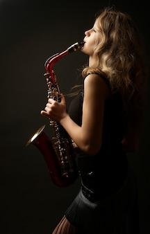 Portret seksowne atrakcyjne kobiety z saksofonem