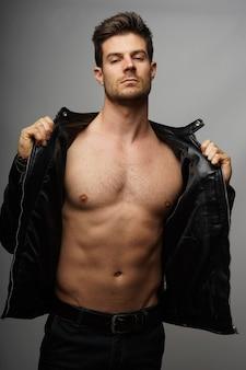 Portret seksownego mężczyzny bez koszuli z idealnym ciałem i skórzaną kurtką