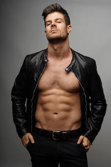 Portret seksownego młodego faceta z muskularnym ciałem w kurtce motocyklowej