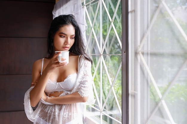 Portret seksownej azjatki w białej bieliźnie nocnej stojącej obok okna i picia kawy w godzinach porannych
