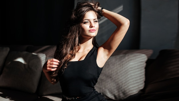 Portret seksownej brunetki w czarnej sukience na ciemnym tle dziewczyna powoli zdejmuje sukienkę