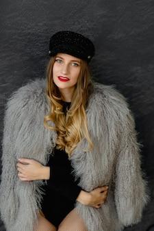 Portret seksownej dziewczyny w czarnej czapce i szarym płaszczu lamy, body i koronkowych rajstopach.