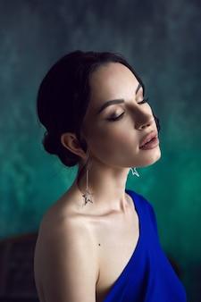 Portret seksownej dziewczyny z kolczykami w postaci gwiazdek w niebieskiej sukience na przetartej ścianie