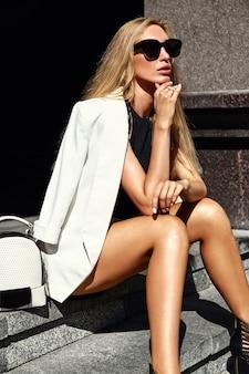 Portret seksownej mody bizneswomanu nowożytny model w białym kostiumu obsiadaniu na schodkach na ulicie z torebką