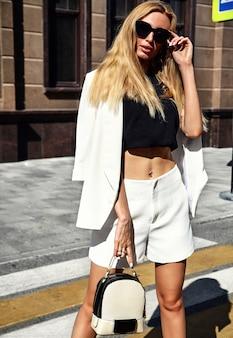 Portret seksownej mody bizneswomanu nowożytny model w białym kostiumu pozuje na ulicznym tle z torebką