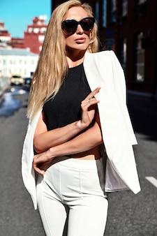Portret seksownej mody bizneswomanu nowożytny model w białym kostiumu pozuje na ulicznym tle za niebieskim niebem