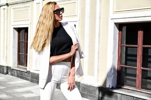 Portret seksownej mody bizneswomanu nowożytny model w białym kostiumu pozuje na ulicznym tle