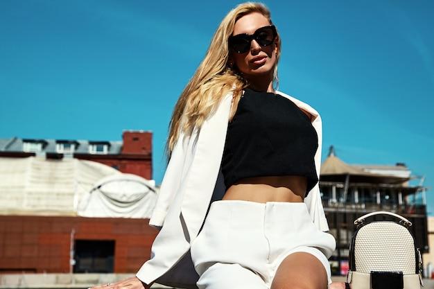 Portret seksownej mody bizneswomanu nowożytny model w białym kostiumu z torebką pozuje na ulicznym tle za niebieskim niebem