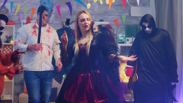 Portret seksownej złej czarodziejki tańczącej na imprezie halloweenowej w otoczeniu przyjaciół w udekorowanym domu