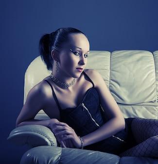 Portret seksowni potomstwa modeluje na kanapie