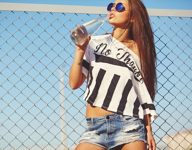 Portret seksowny glamour stylowy piękny młoda kobieta model w jaskrawym modnisia lata przypadkowych ubraniach pozuje na ulicie za żelazną kratownicą i niebieskim niebem. woda pitna z butelki