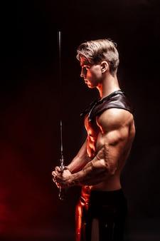 Portret seksowny mięśni skoncentrowany mężczyzna trzyma miecz.