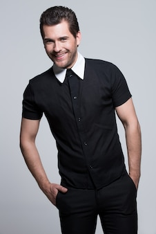 Portret seksowny młody szczęśliwy człowiek w czarnej koszuli z rękami w kieszeniach pozuje na szarej ścianie.