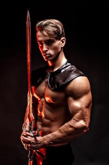 Portret seksowny muskularny mężczyzna trzyma miecz