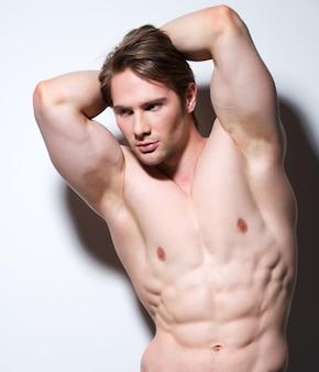 Portret seksowny muskularny młodzieniec pozuje na białej ścianie z kontrastowymi cieniami.