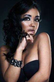 Portret seksowny piękny młody azjata model z pająkiem